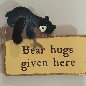 Small Bear hugs wood and a metal sign